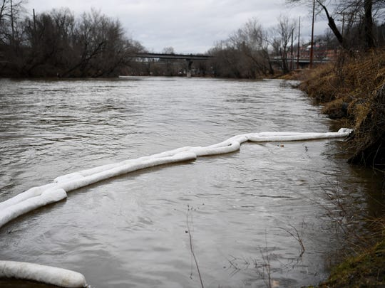 Booms float on the French Broad River across the street from Mountain Energy February 7, 2018, where it is estimated thousands of gallons of petroleum fuel spilled into the river.