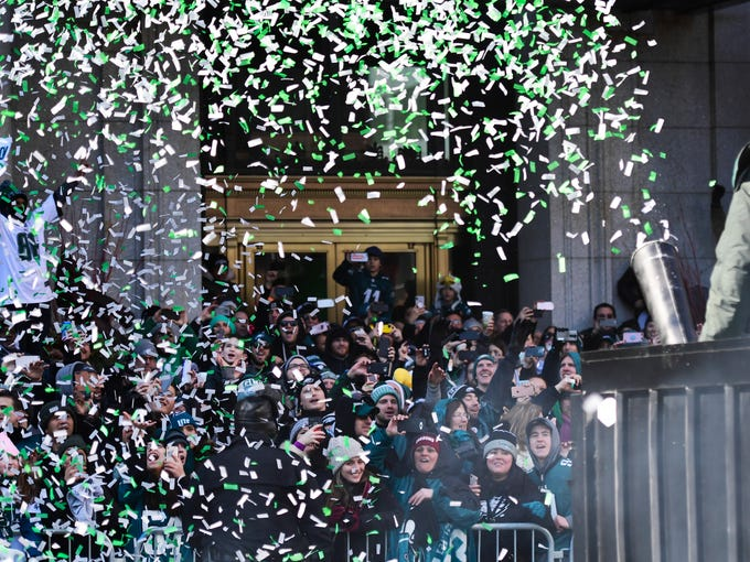 Eagles fans are doused with ticker tape confetti during