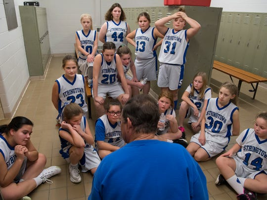 Stringtown Elementary School gym teacher Jim Schmidt gathers his 5th-grade girls basketball team in the locker room at halftime to go over their game plan against Highland Thursday night, Jan. 8, 2018.