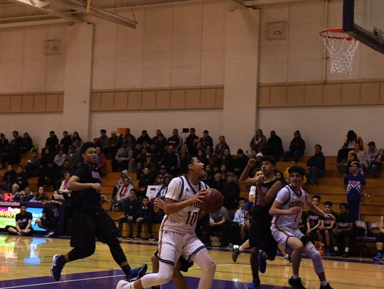 Junior guard AJ Saldana drives to the basket in the