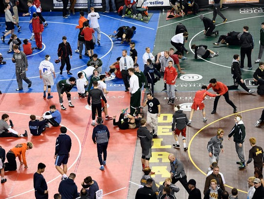 Wrestlers warm up before the preliminary round on the