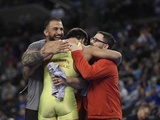 Bergen Catholic's Jacob Cardenas hugs his coaches after winning the 195-pound title  during the NJSIAA state wrestling championships in Atlantic City, NJ on Sunday, March 4, 2018. Cardenas won by major decision, 10-2.