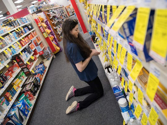 CVS employee Kaylee Merrick, 24, changes the price on some of the items for sale on the shelves at her CVS in Stafford, Va.