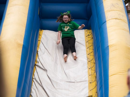 A child slides down an inflatable slide during Knoxville's St. Patrick's Day festivities March 17, 2018.
