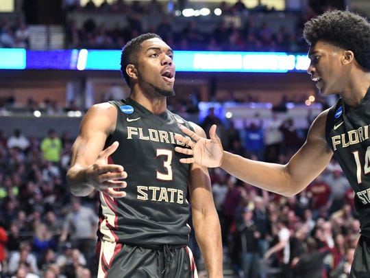 FSU sophomore guard Trent Forrest and junior guard Terance Mann celebrating after Trent Forrest scored a layup while getting fouled.