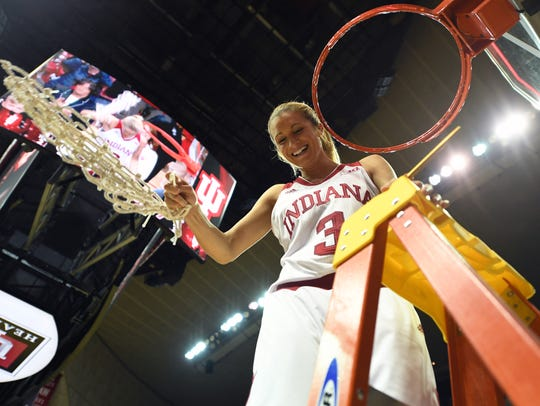 IU guard Tyra Buss cuts down the net after the Hoosiers won their first WNIT championship.