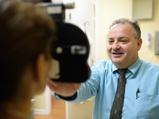Dr. Michael Carelli gives a patient an eye exam at
