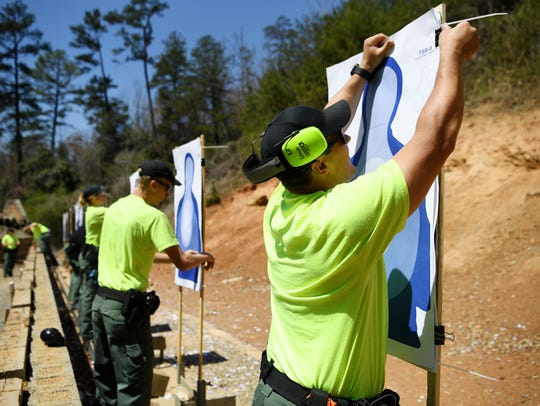 Hunter Hamm prepares a target at a firing range in Sylva April 12, 2018. Hamm is a student in the National Park Service Seasonal Law Enforcement Training Academy's 100th class.