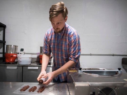 Nathan Hilbert, owner and operator of Unrefined Chocolate, demonstrates his chocolate making process in North Knoxville on Wednesday, April 25, 2018.