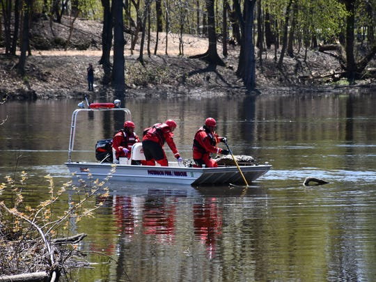 A search crew appears to drag a body out of the Passaic