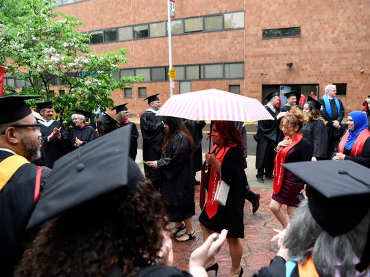 Class of 2018 graduates walk through the rain into the Passaic County Community College commencement in Paterson, NJ on Thursday, May 17, 2018.