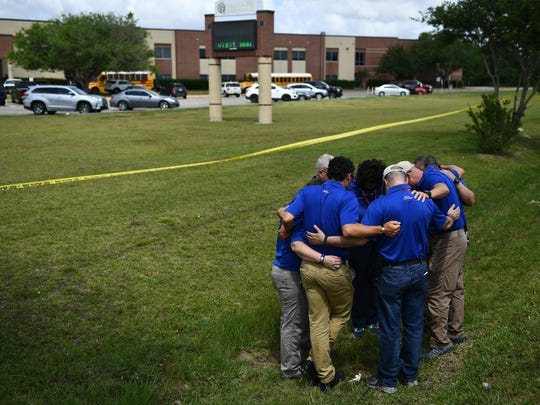 Chaplains from the Billy Graham Rapid Response Team pray on the grounds of Santa Fe High School on May 19, 2018, in Santa Fe, Texas. Ten people, mostly students, were killed when a teenage classmate armed with a shotgun and a revolver opened fire at the school on May 18. The gunman, arrested on murder charges, was identified as Dimitrios Pagourtzis, a 17-year-old junior at Santa Fe High School. He is being held on capital murder charges, meaning he could face the death penalty.