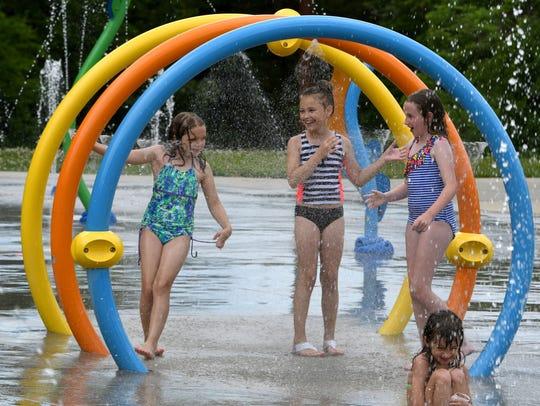 Kids enjoying the splash pad at McFee Park Monday,