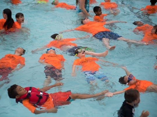 Children from Camp Wallace in Knoxville practice floating on their backs at a giant swim lesson held by Dollywood's Splash Country in its wave pool at its annual water safety day Thursday, June 21, 2018.
