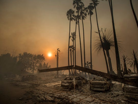 FILE - In this Dec. 5, 2017 file photo, smoke rises behind a destroyed apartment complex as a wildfire burns in Ventura, Calif. In the 30 years since 1988, the number of acres burned in the U.S. by wildfires has doubled.