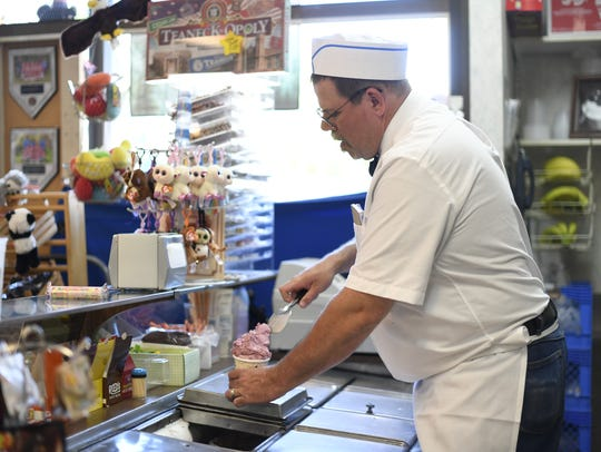 Steven Mather helps a customer in Bischoff's Confectionery
