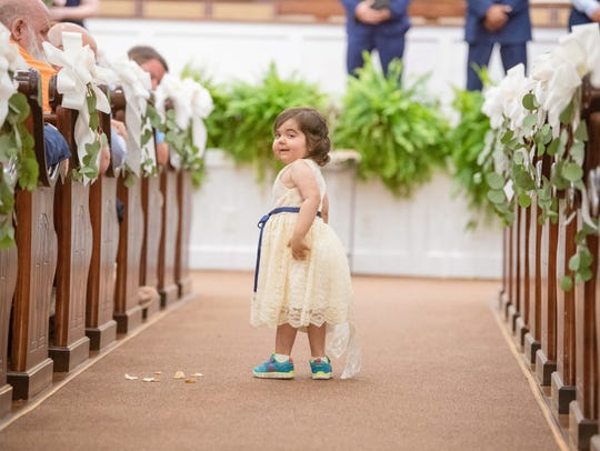 Skye Savren-McCormick of Ventura pauses during her duties as flower girl at Hayden Ryals wedding in Alabama. Ryals donated her bone marrow to Skye, who was born with a rare form of leukemia.