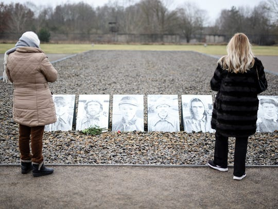 Visitors stand in front of pictures of prosecuted persons on Jan. 27, 2018, at a place where in 1941 more than 10,000 Soviet prisoners of war were executed by being shot in the neck at the former concentration camp Sachsenhausen in Oranienburg near Berlin.