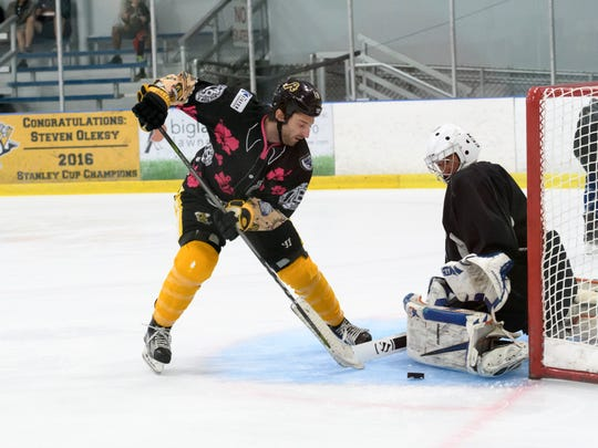 Blake Christensen tries to get the puck around goalie Justin Sand during an Eastside Elite Hockey League summer league game Sunday at the Mount Clemens Ice Arena