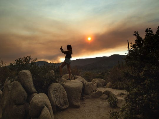 Mara Schumann photographs a plume of smoke from the Ferguson Fire in Yosemite National Park, Calif., on July 24, 2018.