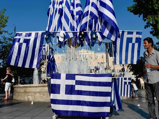 A man sells greek flags during a protest against Greece's
