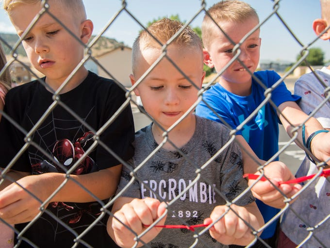 Fiddlers Canyon Elementary School students tie ribbons