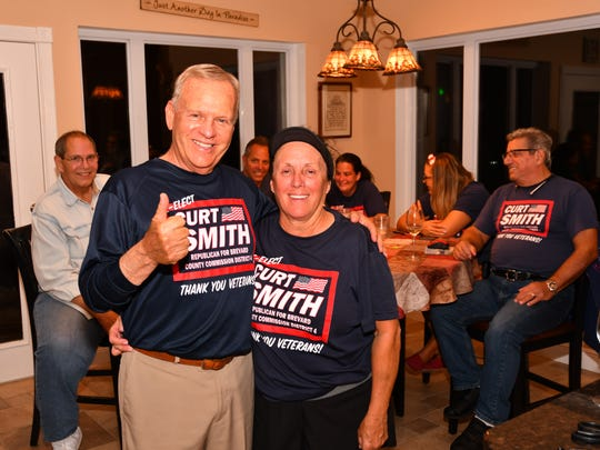 Curt Smith with his wife Linda celebrating his county commission race victory with a few supporters at his Melbourne home Tuesday night.