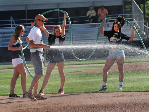 Noblesville groundskeeper Josh Wiegel is assisted by baseball managers Sarah Knight, left, Mweghan Lutz and Aylssa Lacey as they prepare the field for the ISHAA Baseball Sectional gme between Noblesville and Hamilton Southeastern at Noblesville Tuesday June 3, 2014.