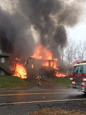 A firefighter walks up a driveway as an apartment building burns in Akron, Ohio, Tuesday, Nov. 10, 2015, where authorities say a small business jet crashed. The plane burst into flames and disintegrated after impact. It was unclear how many people were on board. (Scott Ferrell via AP)