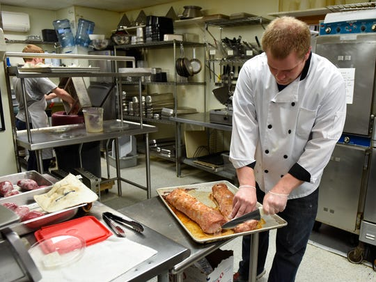 Bill Dotlevson starts carving pork loin for dinner Saturday, Aug. 12, at Coyote Moon Grille, in St. Cloud.