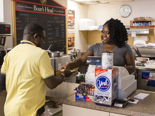 Anastaza Duncan serves a customer at Scott's across from the DuPont Building in Wilmington on Wednesday.