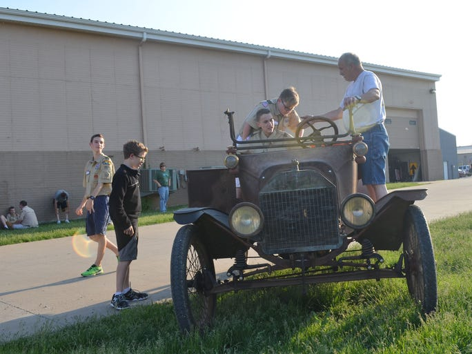 Volunteer Lee Votroubek helps Boy Scouts from Coralville Troop 207 into a Model T on May 29 outside the Antique Car Museum of Iowa in Coralville.