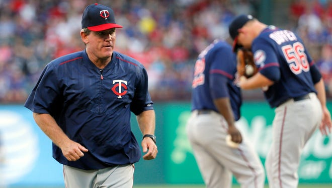 Minnesota Twins pitching coach Neil Allen jogs back to the dugout after paying starting pitcher Tyler Duffey a visit on the mound in the first inning of a baseball game against the Texas Rangers on Thursday, July 7, 2016, in Arlington, Texas. (AP Photo/Tony Gutierrez)