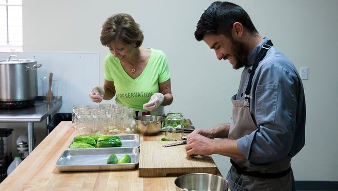 Chef Ryan Harrison (right) and his mother Gina Harrison prepare a batch of Jersey Gina's Gems garlic dill pickles inside Preservation Handcrafted Foods in Westmont.
