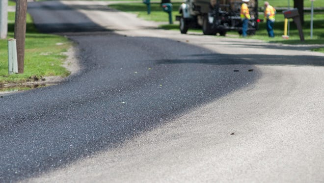 In this July 2014 photo, one side of East Minges Road is coated with a layer of fog seal treatment. Crews will hit some 30 roads this summer with pavement repairs.