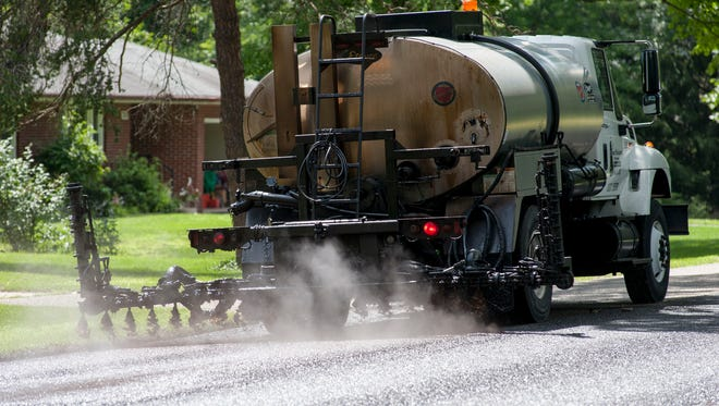 A truck applies a fogseal treatment on East Minges Road in 2014.
