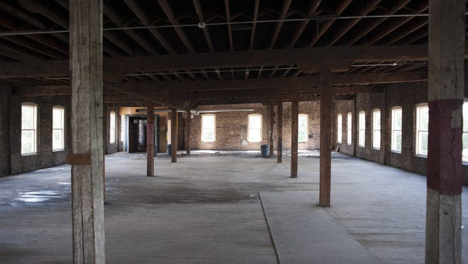 In this July 2014 photo, columns and exposed-brick walls at the empty riverfront building at 15 Carlyle St.
