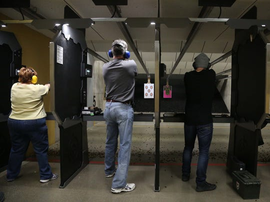 People shoot at targets in the CrossRoads Shooting Sports shooting range on Sunday, Jan. 10, 2016, in Johnston.