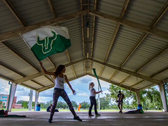 Ashley Reinke, left, and Madison Bonnell, both members of the University of South Florida's color guard, practice their routines Wednesday Sept. 28, 2016, near the university's stadium in Hillsborough County.