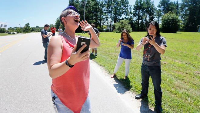 Netsertive employees, Jenny Bramble, left, Sarah Palmer, center, and Fu Thong, right, play Pokemon Go while taking a quick break from their office on July 28, 2016 in Morrisville, N.C.