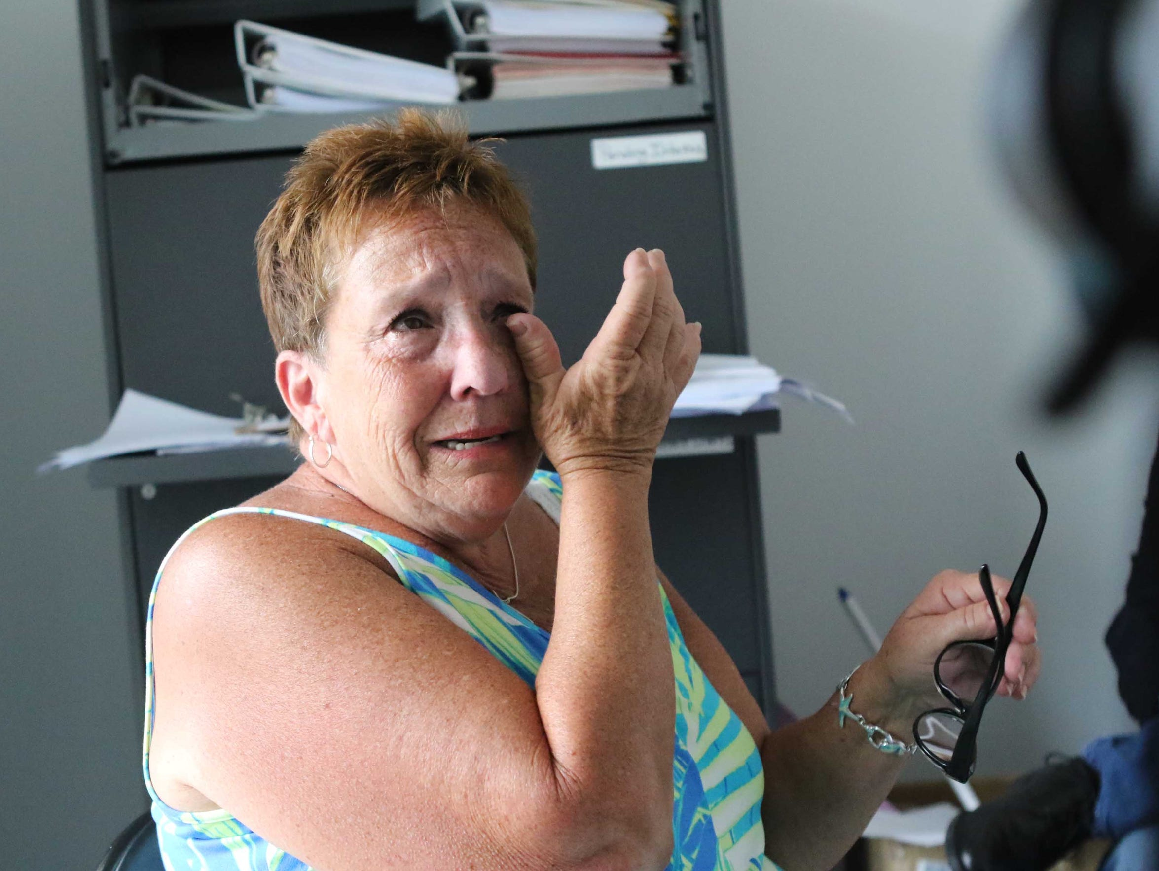 Donna Osman, 64, of Lewes, wipes away tears while telling