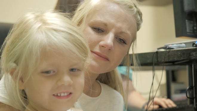 Cantonment resident Brittany Magilke cries tears of joy after her daughter, McKinley Ward's, cochlear implants are turned on Wednesday at Nemours Children's Specialty Care in Jacksonville.