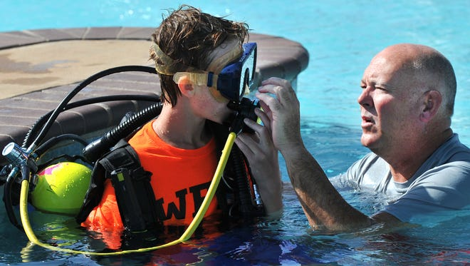 Wichita Falls police dive team member Sammy Motsenbocker teaches Junior Citizen's Academy student B.J. Zinnai how to breathe through a underwater oxygen mask during a previous JCPA.