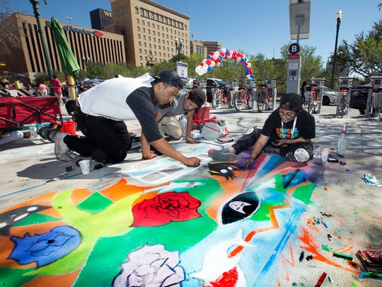 """Carlos Zubia, left, and Fernando Leyva, center, help artist Cindy Martinez with her chalk art they called """"Road Trip"""" depicting flowers, a classic Volkswagen bus and other things they imagined during the 2016 Chalk the Block in Downtown El Paso."""