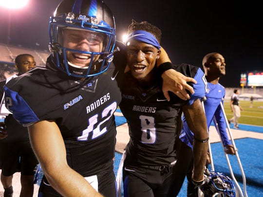 MTSU's Brent Stockstill (12) and Jeremy Cutrer (8) come off the field celebrating their win over Louisiana Tech 38-34, on Saturday, Sept. 24, 2016.