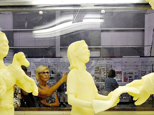 Wanda Wandress of Springettsbury Township looks at the butter sculpture during the first day of the York Fair on Friday.