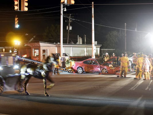 MYERSTOWN CRASH -- A horse and buggy gallop past the scene of a crash as firefighters clear debris at 8:53 p.m. Wednesday at routes 422 and 501. The westbound lanes of Route 422 were closed briefly. A police report was not available.