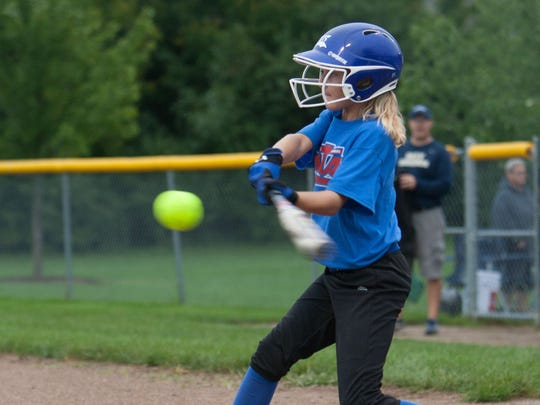 Olivia Bucher, 12, swings at a pitch at the first Play for Peyton Memorial Softball Tournament at Hamilton Southeastern High School, Fishers, on Sept. 6, 2014. The HSE-Fishers Youth Softball League hosted the tournament to raise awareness for mental illness and the risk of suicide. The tournament is dedicated in memory of Peyton Riekhof, who died from suicide in 2013.