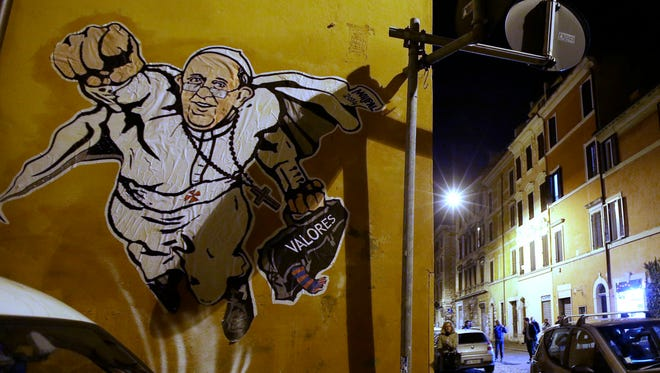 "Graffiti depicting Pope Francis as Superman and holding a bag with a writing which reads: ""Values"" is seen on a wall of the Borgo Pio district near St. Peter's Square in Rome."