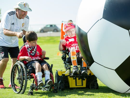 Bob Bigney, NM Youth Soccer Association technical director, left, assists Nathaniel Sidwell, 6, of Las Cruces, center, and Chase Anthony-McLain, 6, of Chamberino, New Mexico, right, play with an oversized inflatable soccer ball on Saturday August 26, 2017 during Las Cruces Timbers Football Club's soccer camp for special needs kids at the High Noon Soccer Fields.
